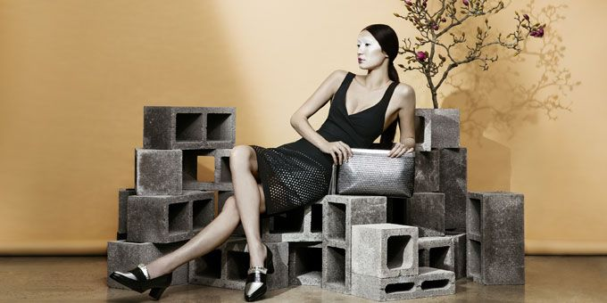 Women modeling shoes against concrete bricks