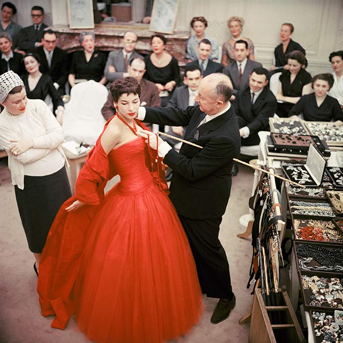 EXHI043360  Christian Dior adjusts the accessories to the Zaire dress, on his star model Victoire, during rehearsal for the autumn−winter 1954, haute couture show Photo © Mark Shaw/mptvimages.com