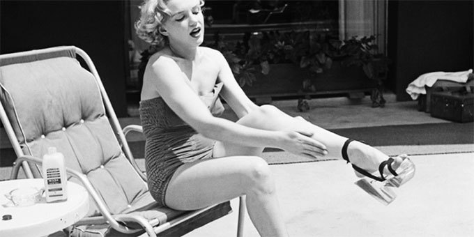 Marilyn Monroe trying on shoes