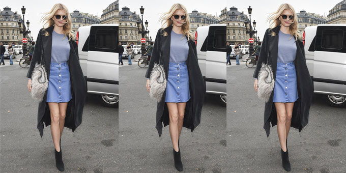 street style photo of model wearing denim skirt, ankle boots, statement bag and black coat